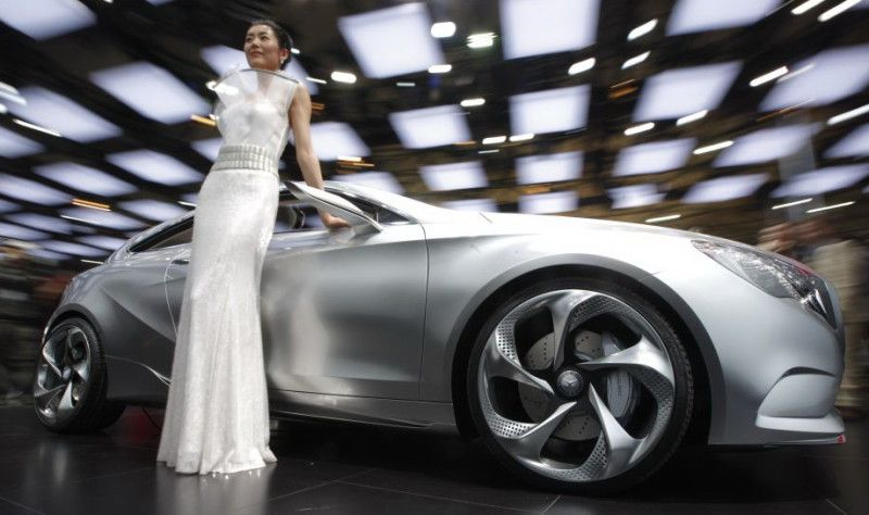 a model poses next to a mercedes benz concept a-class during the opening day of the shanghai auto show